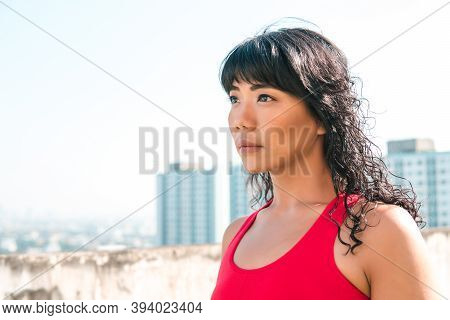 Young Asian Woman Looking Far Distance Into The Skyline Buildings At Rooftops. Female Athelete Deter