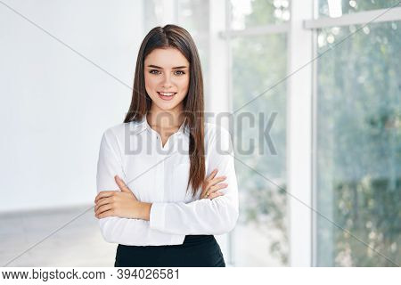 Smiling Confident Pretty Businesswoman With Crossed Arms Posing In A Modern Office With Copy Space.