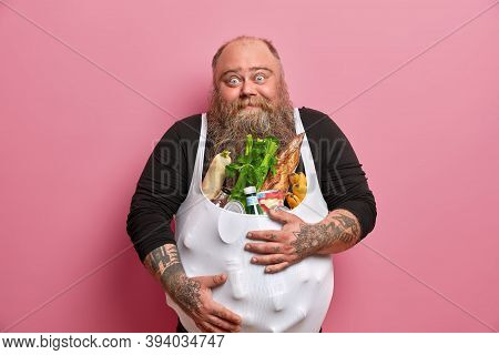 Obese Bearded European Man Has Excess Weight Because Of Unhealthy Harmful Nutrition, Carries Differe