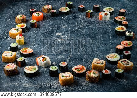 Set Of Traditional Japanese Food On A Dark Background. Different Sushi Rolls In A Circle With Copy S