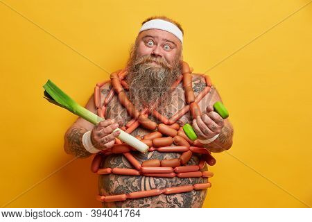 Funny Fatso Guy Poses With Sport Equipment And Green Leek, Wrapped By Sausages, Tries To Eat Healthy