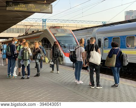 People On The Platform Of The Station Are Waiting For The Train. Men And Women Meet An Approaching T