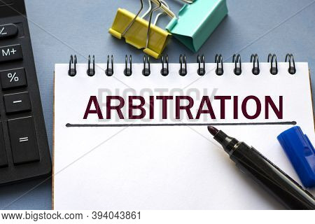 Arbitration Word Is Written In A Notebook With A Marker, Calculator, Clamps And Cactus. Business Con