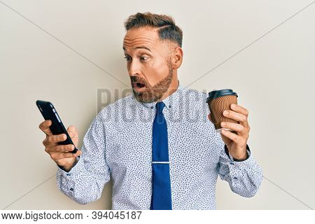 Handsome middle age business man using smartphone and drinking a cup of coffee afraid and shocked with surprise and amazed expression, fear and excited face.