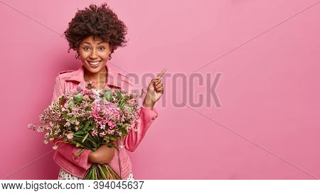 Studio Shot Of Pretty Dark Skinned Woman With Bunch Of Beautiful Flowers, Shows Direction, Points On