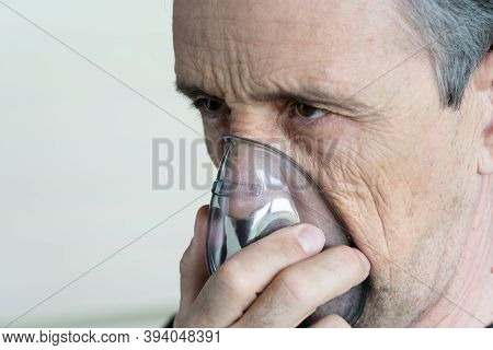 Medical Oxygen Mask On A Man. A Man Breathes Oxygen Using A Mask. Close-up Of An Old Man Doing Inhal