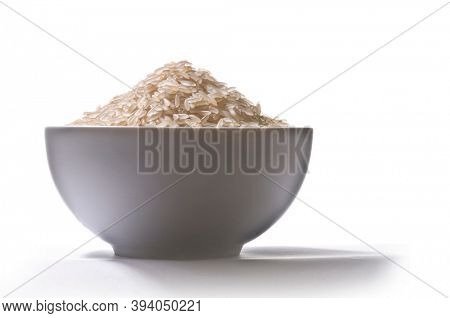 Cup filled with raw rice grains, lateral view, on white background and shadow