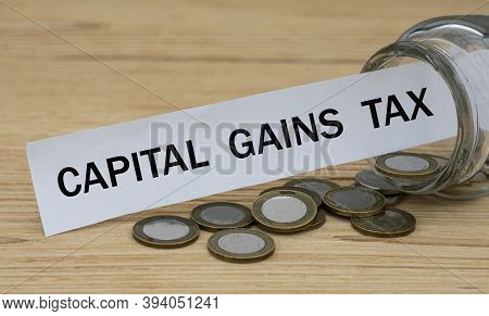 Capital Gains Tax - Words On A White Strip Of Paper With A Can Of Money. Business And Finance Concep