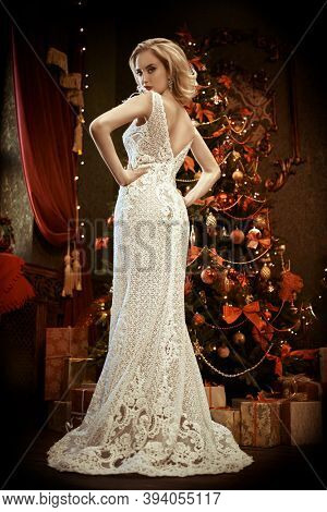 Christmas and New Year celebration concept. Charming young woman in luxurious evening dress and with beautiful evening makeup and hairstyle meets Christmas at the New Year tree. X-mas fashion concept.