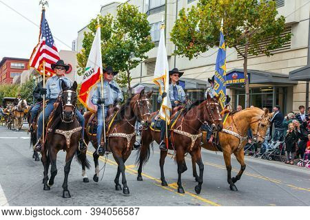 SAN FRANCISCO, USA - OCTOBER 11, 2009: Columbus Day celebration. Equestrian parade in honor of the national holiday. Dressy riders in cowboy hats carry US flags on beautiful horses.
