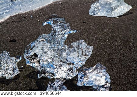 Iceland. The famous icelandic black sand beach. Ocean surf brings ice floes. Cold day in North Atlantic. The concept of extreme, northern and photo tourism