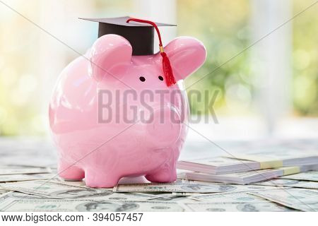 Piggy bank with a graduation mortar board cap concept for the cost of a college education