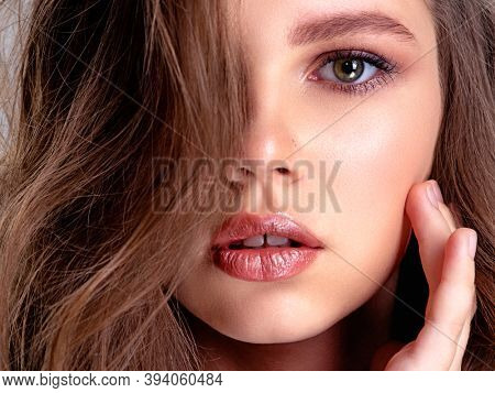 Closeup of face of a beautiful brown-hair girl with long, wavy hair. Fashion model  with smokey eye makeup. Attractive woman with makeup looking at the camera. Pretty caucasian girl with healthy skin.