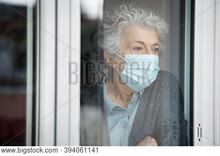 Lonely old woman wearing surgical mask and looking through the window during lockdown. Senior sad woman with face protective mask stay at home. Depressed lady at home during the covid-19 pandemic.