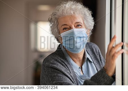 Portrait of smiling senior woman wearing face mask near window. Old woman wearing surgical mask and looking at camera during the lockdown. Happy elderly lady during the covid-19 pandemic stay at home.