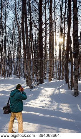 Exotic trip to the Arctic. Tourist with a photo bag photographs of the winter forest. Sunset in the winter forest. Travel to Lapland. The sun is low on the horizon.