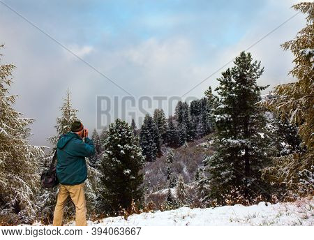 Tourist - photographer in a jacket and hat photographs the magnificent landscape. Giau Pass, Dolomite Alps. Huge evergreen spruce covered with first snow. Concept of active and photo tourism
