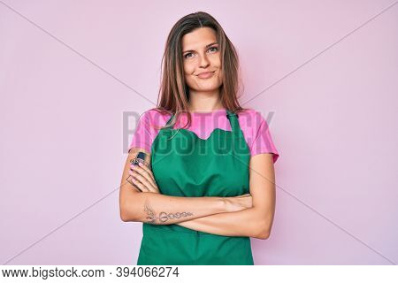Beautiful caucasian woman wearing professional apron skeptic and nervous, disapproving expression on face with crossed arms. negative person.