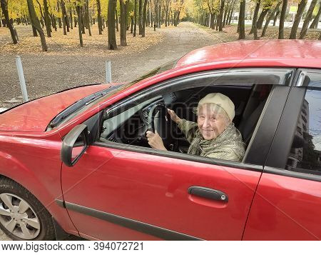 The Smiling Elderly Woman In A Red Jacket At The Wheel The Car