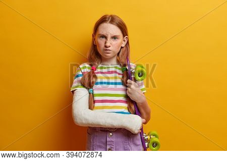 Annoyed Little Girl With Ginger Hair And Freckles, Smirks Face And Has Dissatisfied Expression, Pose