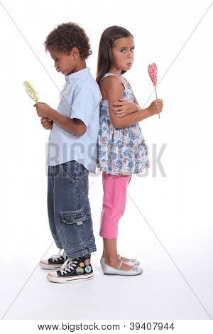a little boy and a little girl pouting and eating ice cream