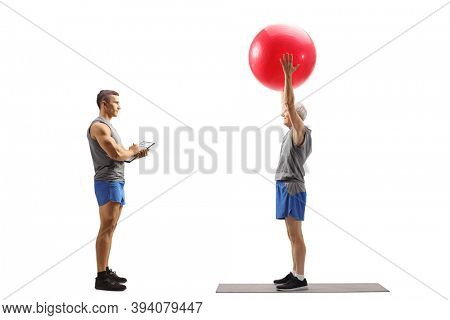 Full length profile shot of an elderly man exercising with a fitness ball with a personal fitness instructor isolated on white background