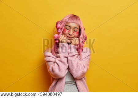 Horizontal Shot Of Satisfied Pleased Pink Haired Asian Woman Keeps Hands Under Chin, Closes Eyes, Ap
