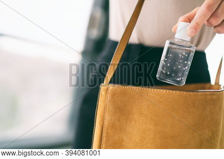 COVID-19 hand sanitizer woman using small sanitiser bottle in bag when going out walking to work in public for washing hands disinfecting with alcohol gel dispenser.