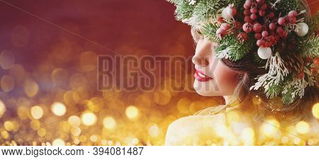 Beautiful girl with Christmas spruce wreath on her head on a background of sparkling festive lights. The atmosphere of magic. Christmas winter beauty woman. Copy space.