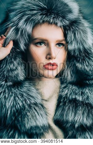 Portrait of a gorgeous fashionable woman in a silver fox fur coat with hood. Winter fur coat fashion.