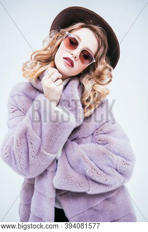 Portrait of a glamorous blonde girl posing in a luxury mink coat on a light background. Fur coat fashion. Studio portrait.