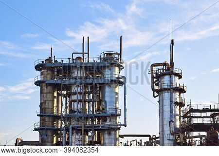 Old Distillation Column Towers With Blue Sky With Clouds Background At Chemical Plant. Exterior Of S