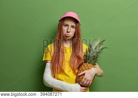 Sad Offended Freckled Redhead Girl Being Punished By Parents, Holds Juicy Pineapple, Purses Lips And