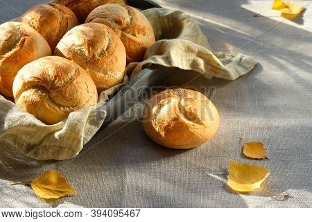 Kaiser, Or Vienna Buns In Bread Basket On Linen Textile Background With Yellow Autumn Leaves.