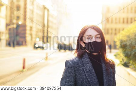 Redhead Caucasian Woman On A Bright Sunny Empty Street In Black Protective Mask. Revival After Coron