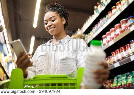 Happy Black Lady Using Cellphone With Grocery Shopping Checklist Application Buying Food Products In