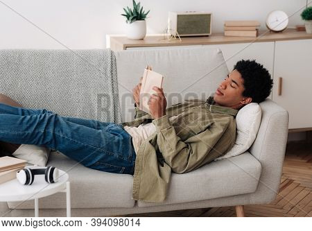 Distance Education Concept. Focused Black Teen Student With Textbook Reading On Sofa At Home. Africa