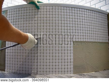 Laying Ceramic Tiles In The Bathroom Of A Residential Building. Installing Stone Glass Mosaic Tile
