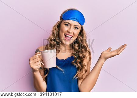 Young blonde girl wearing sleep mask and pyjama drinking coffee celebrating achievement with happy smile and winner expression with raised hand