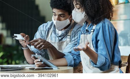 Stressed Millennial African American Couple In Protective Masks And Aprons Because Of Economic Condi