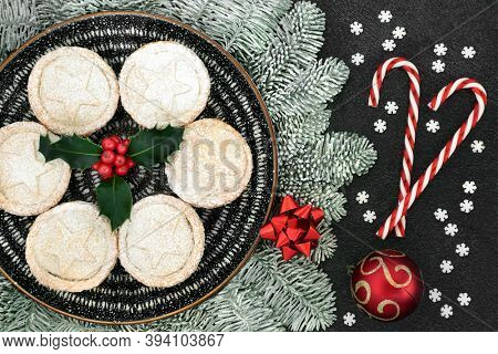Christmas homemade mince pies on a plate with holly, snow covered fir, candy canes snowflake & bauble decorations on grey grunge background. Festive food composition. Flat lay, top view.