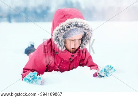Funny Caucasian Smiling Girl In Warm Winter Clothes Pink Jacket Playing With Snow. Cute Child Lying