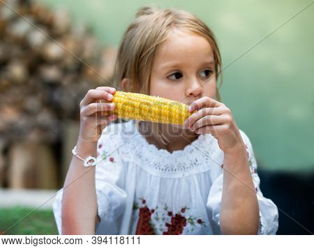 Pensive Girl 5 Years Old Eats Grilled Corn.close-up Hands With Corn, Blurred  Face And Background.