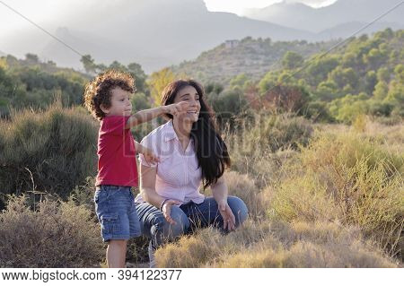 Mother And Son On Excursion In The Field Crouching Down And Observing In The Distance The Indication