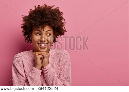 Studio Shot Of Attractive Ethnic Curly Woman Looks Gladfully Aside, Keeps Hands Under Chin, Has Toot