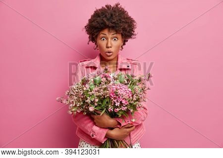 Surprised Ethnic Woman With Floral Bunch, Has Shocked Expression, Comes On Romantic Date, Receieves