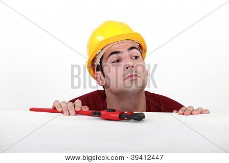 Curious tradesman peering over a ledge