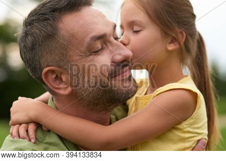 Cute Little Girl Hugging And Kissing Her Happy Dad While Spending Time Together Outdoors On A Warm D
