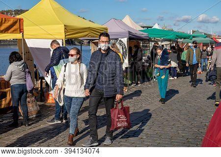 Prague, Czech Republic - October 24, 2020: People In Face Masks Strolling Through The Naplavka Farme