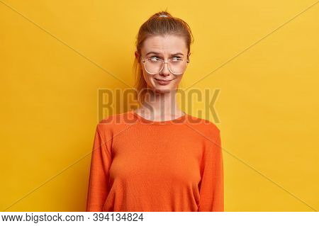 Photo Of Thoughtful Good Looking Nerdy Girl In Spectacles, Has Thoughtful Expression, Concentrated A
